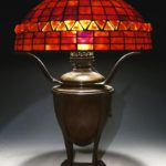 A Tiffany Studios Leaded Glass & Ember-Like Glass On Bronze Converted Oil Lamp Base. Sold For $14,100.